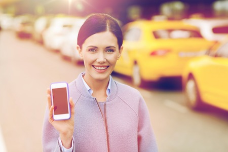 smiling woman showing smartphone over taxi in city Stock Photo