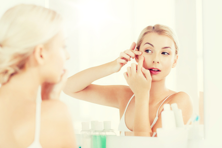 daily room: woman squeezing pimple at bathroom mirror