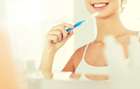 grooming: woman with toothbrush cleaning teeth at bathroom