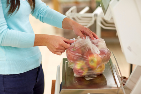 Femme pesant pommes sur échelle à magasin d & # 39 ; épicerie Banque d'images - 80249935