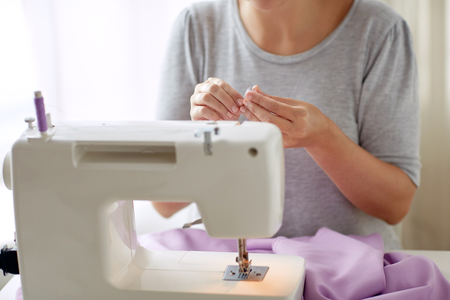 woman with spool of thread and sewing machine Stock Photo