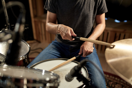 male musician playing drums and cymbals at concert