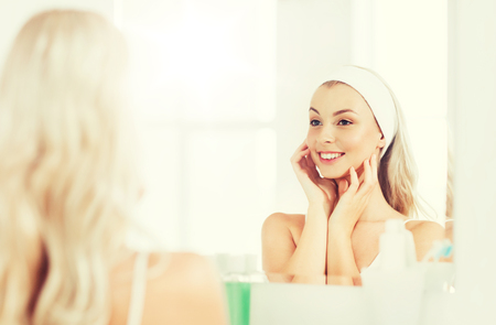 daily room: woman in hairband touching her face at bathroom