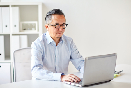 businessman in eyeglasses with laptop office Imagens