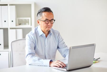 Uomo d'affari in occhiali con ufficio portatile Archivio Fotografico - 80232963