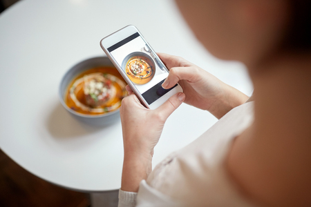 woman with smartphone photographing food at cafe Фото со стока