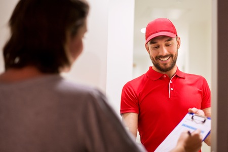 deliveryman with clipboard at customer home Stock Photo