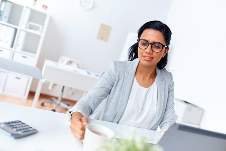 businesswoman drinking coffee or tea at office