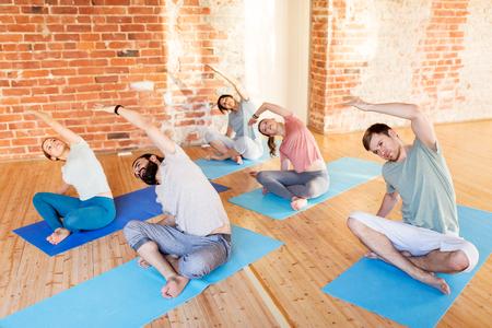 Grupo de personas haciendo ejercicios de yoga en el estudio Foto de archivo - 80282638