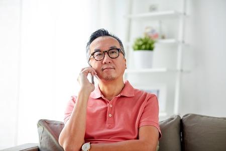 gelukkig man belt op smartphone thuis