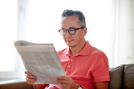 happy man in glasses reading newspaper at home Stok Fotoğraf