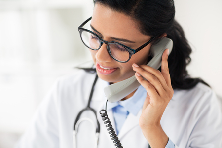 doctor in glasses calling on phone at hospital