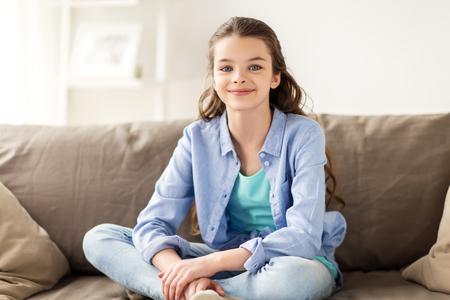 Feliz niña preadolescente sonriente sentado en el sofá en casa Foto de archivo - 80232917