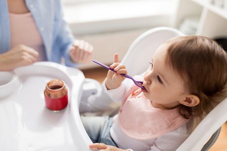 babymeisje met lepel eet puree van jar thuis Stockfoto