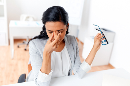 businesswoman rubbing tired eyes at office Stock Photo - 80230265