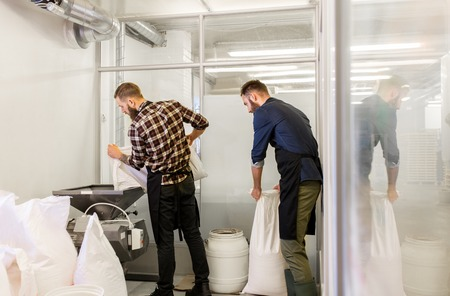 the brewer: men with malt bags and mill at craft beer brewery Stock Photo