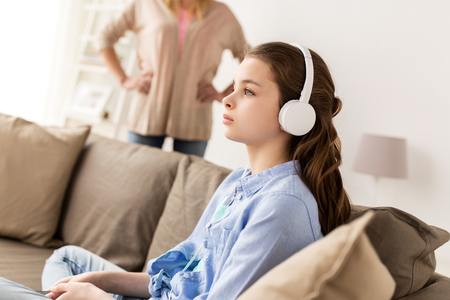 girl with earphones and angry mother at home