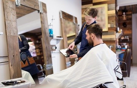 barber showing tablet pc to man at barbershop Фото со стока