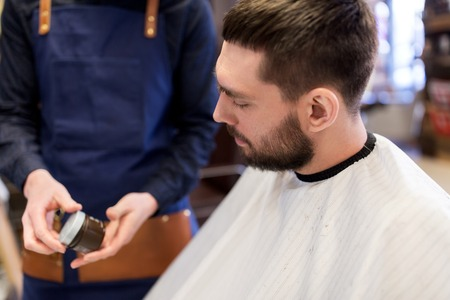 grooming: barber showing hair styling wax to male customer Stock Photo