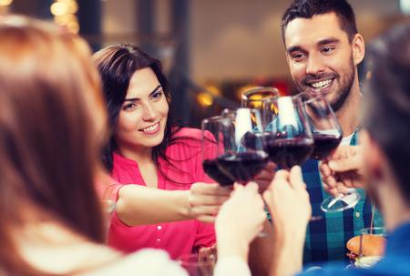 レジャー、お祝い飲み物、人々、休日コンセプト - 幸せなカップルや友人のレストランでワインのグラスをチャリン