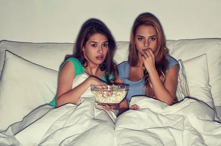 우정, 사람, 파자마 파티, 엔터테인먼트 및 정크 푸드 개념 - 무서 워 친구 또는 십대 여자 팝콘을 먹고 집에서 tv에 공포 영화를보고