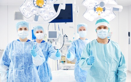 theatre masks: surgery, medicine and people concept - group of surgeons in operating room at hospital showing thumbs up Stock Photo