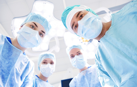 theatre masks: surgery, medicine and people concept - group of surgeons in operating room at hospital looking into camera Stock Photo
