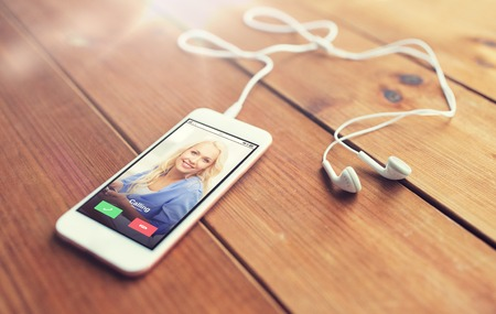technology, communication, gadget and object concept - close up of white smartphone and earphones on wooden surface with incoming call on screen