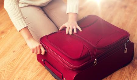 여름 휴가, 여행, 관광 및 개체 개념 - 짐 포장 및 휴가를위한 여행 가방을 압축을 닫습니다