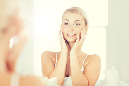 grooming: beauty, hygiene, morning and people concept - smiling young woman looking to mirror at home bathroom