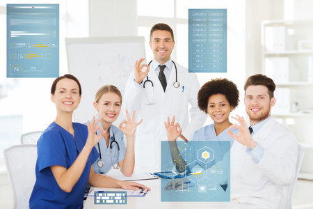 medicine, healthcare, technology and people concept - group of happy doctors meeting on presentation or conference at hospital and showing ok hand sign Stock Photo