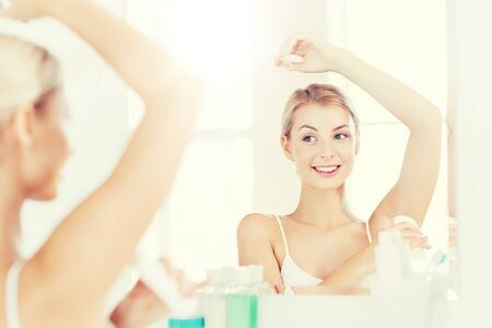beauty, hygiene, morning and people concept - smiling young woman applying antiperspirant or stick deodorant and looking to mirror at home bathroom