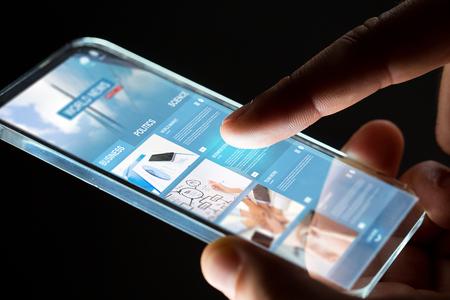concetto di business, persone, mass media e tecnologia - mani con la pagina web di affari sullo schermo dello smartphone su sfondo nero