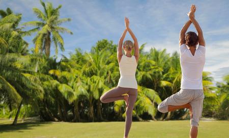 フィットネス、スポーツ、人々 の概念 - 幸せなカップル ヨガ、ヤシの木とエキゾチックな自然な背景の上で瞑想