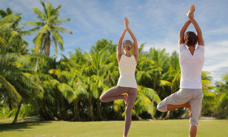 fitness, sport and people concept - happy couple making yoga and meditating over exotic natural background with palm trees