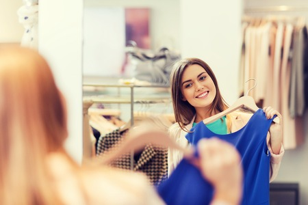 happy woman with clothes at clothing store mirror