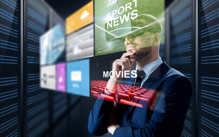domain: business, people and technology concept - businessman in virtual reality headset with multi media projection over futuristic server room background Stock Photo