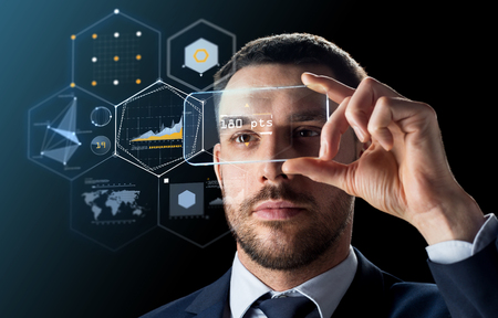 business, augmented reality and future technology concept - businessman in suit working with transparent smartphone and virtual charts projection over black background