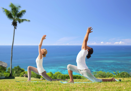 fitness, sport, relax and people concept - couple making yoga in low lunge pose over exotic natural background with palm tree and ocean Stock Photo