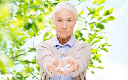 age, healthcare and medicine concept - senior woman with pills over green natural background
