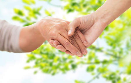 age, generation and care concept - close up of senior woman and young woman holding hands over green natural background