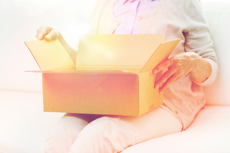 age, delivery, mail, shipping and people concept - close up of senior woman looking into open parcel box at home