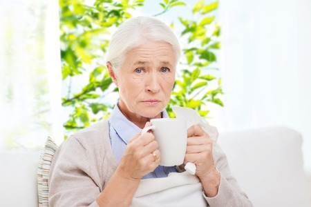 healthcare, age and people concept - sick senior woman with paper napkin drinking hot tea at home over window with green natural background