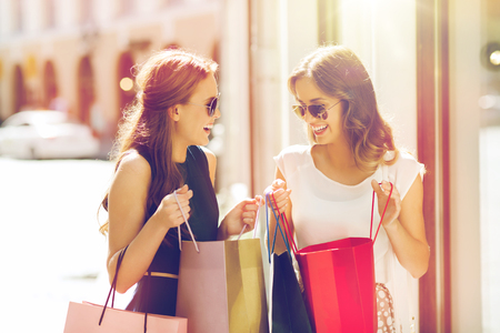 sale, consumerism and people concept - happy young women with shopping bags talking at shop window in city Stock Photo