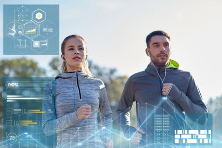 warming up: fitness, sport and people concept - happy couple running and listening to music in earphones outdoors Stock Photo