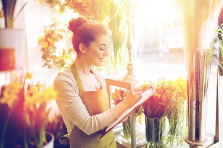 Les gens, la vente, la vente au détail, d'affaires et le concept de fleuristerie - heureuse femme souriante de fleuriste avec l'écriture et de prendre des notes de presse-papiers commander au magasin de fleurs Banque d'images - 80276624