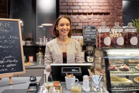 saleslady: happy woman or barmaid with cashbox at cafe