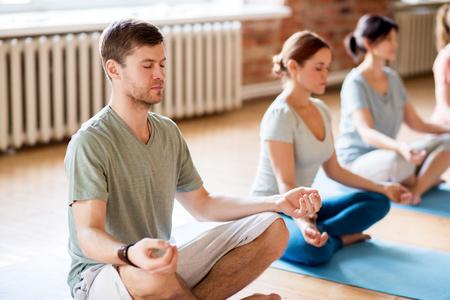 フィットネス、ヨガ、健康的なライフ スタイル コンセプト - ロータス瞑想の人々 のグループは、スタジオでポーズします。