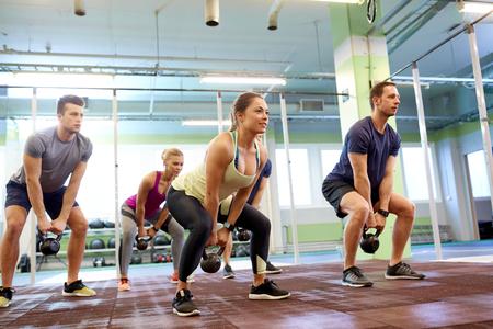 sport, fitness, gewichtheffen en training concept - groep mensen met kettlebells en hartslag trackers oefenen in de sportschool Stockfoto