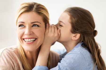 people, trust and family concept - happy daughter whispering secret to her mother Stockfoto